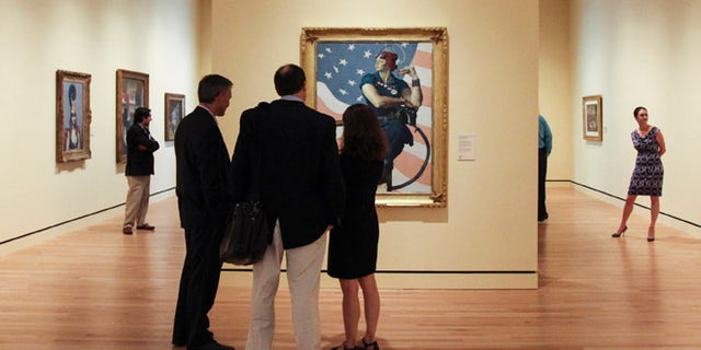 """FILE 2012: Guests observe Norman Rockwell's 1943 oil on canvas painting """"Rosie the Riveter"""" in Bentonville, Arkansas."""