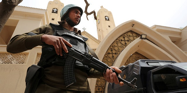 A guard stands outside a Coptic church in Egypt.