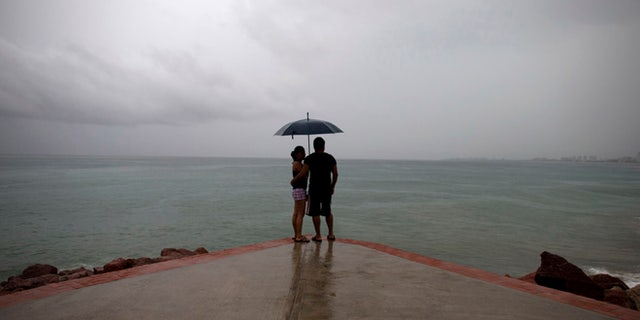 """FILE - In this Friday, Oct. 23, 2015, file photo, a couple looks out to sea as rainfall increases with the approach of Hurricane Patricia in Puerto Vallarta, Mexico. Mexico weathered a record eastern Pacific hurricane season with almost no deaths and relatively little damage, given the intensity of this year's storms. According to the U.S. National Oceanic and Atmospheric Administration's 2015 hurricane season report released Tuesday, Dec. 1, 2015, Patricia was """"the strongest hurricane on record in the Western Hemisphere"""" just before it struck a sparsely populated stretch of Mexico's Pacific coast. (AP Photo/Rebecca Blackwell, File)"""