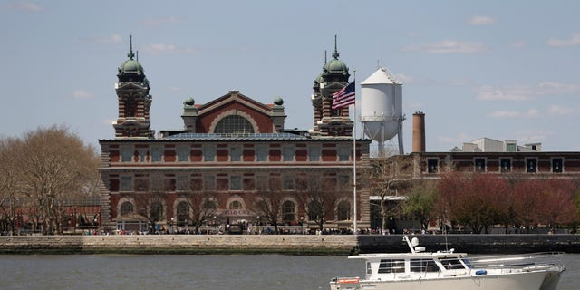 A yacht passes by Ellis Island as it makes its way through New York Harbor.