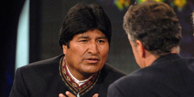 "Bolivian President Evo Morales, left, speaks with Daily Show host Jon Stewart, center, on Comedy Central's ""The Daily Show with Jon Stewart"" in New York, Tuesday Sept. 25, 2007. Morales's translator is seen at right. (AP Photo/Peter Kramer)"