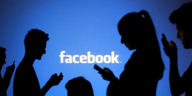 People are silhouetted as they pose with mobile devices in front of a screen projected with a Facebook logo, in this picture illustration taken in Zenica October 29, 2014. Facebook Inc warned on Tuesday of a dramatic increase in spending in 2015 and projected a slowdown in revenue growth this quarter, slicing a tenth off its market value. Facebook shares fell 7.7 percent in premarket trading the day after the social network announced an increase in spending in 2015 and projected a slowdown in revenue growth this quarter.   REUTERS/Dado Ruvic (BOSNIA AND HERZEGOVINA  - Tags: BUSINESS SCIENCE TECHNOLOGY BUSINESS LOGO) - RTR4C0UZ