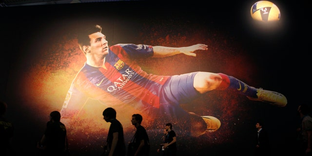 """Visitors walk past a placard of """"FIFA 15"""" video game featuring soccer player Lionel Messi at the Gamescom 2014 fair in Cologne Aug. 13, 2014."""