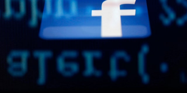 Photo illustration - A Facebook logo on an iPad is reflected among source code on the LCD screen of a computer.