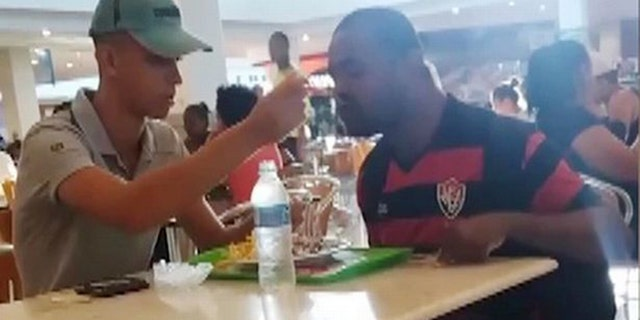 A Brazilian fast food employee has earned high praise online for taking time out of his day to feed a customer with an arm disability.