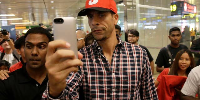 """FILE - In this Tuesday, May 13, 2014, Manchester United's Rio Ferdinand takes a """"selfie"""" upon arrival at the Changi International Airport in Singapore. The English Football Association has banned Queens Park Rangers defender Rio Ferdinand for three games over a tweet containing a derogatory reference to women.  (AP Photo/Wong Maye-E, File)"""