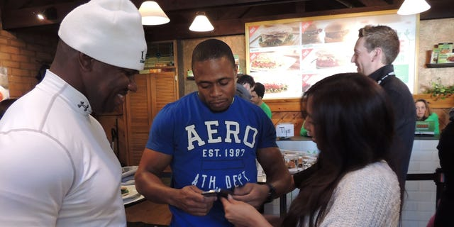 Jan 20, 2014: Jamaican bobsledders Wayne Blackwood, left, and Marvin Dixon, center, talk to an admirer at the MorningStar Veggie Burger Bar in Park City, Utah.