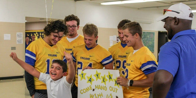 Taylan celebrates after Findlay High School football players invited him to join them on the sidelines this season.