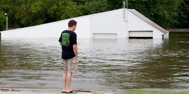 July 24: Sean Herdrich, of Manchester, Iowa, looks at his friend's downtown store for damage after the Maquoketa River flooded the area.
