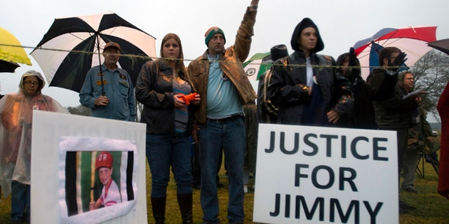 Tim Nowak throws up his arm at the time of the scheduled execution of Juan Carlos Chavez as friends of Jimmy Ryce maintain a vigil  across the highway from the Florida State Correctional Prison near Starke, Fla. Wednesday, Feb. 12, 2014. Chavez was executed Wednesday night for raping and killing 9-year-old boy Jimmy Ryce 18 years ago, a death that spurred the victim's parents to press nationwide for stronger sexual predator confinement laws and better handling of child abduction cases. (AP Photo/Phil Sandlin)