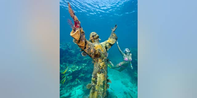 """Katherine Wieland snorkels by the the """"Christ of the Abyss"""" statue, an underwater icon for John Pennekamp Coral Reef State park, off Key Largo, Fla. Named after a former Miami newspaper editor, Pennekamp is the nation's first underwater preserve. FOR EDITORIAL USE ONLY (Stephen Frink/Florida Keys News Bureau)"""