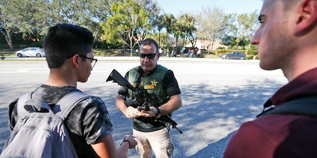 A law enforcement officer talks with students after the shooting at Marjory Stoneman Douglas High School.