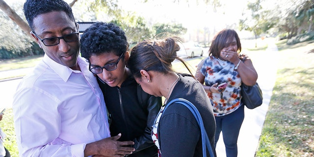 Family members hug a student after he exited Marjory Stoneman Douglas High School on Feb. 14, 2018, in Parkland, Fla.