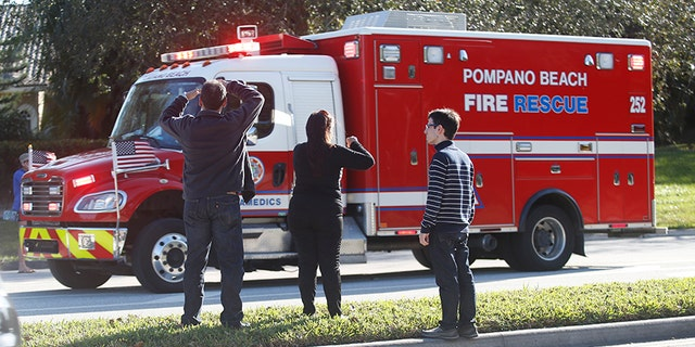 Anxious family members watch a rescue vehicle pass by on Wednesday in Parkland, Fla.