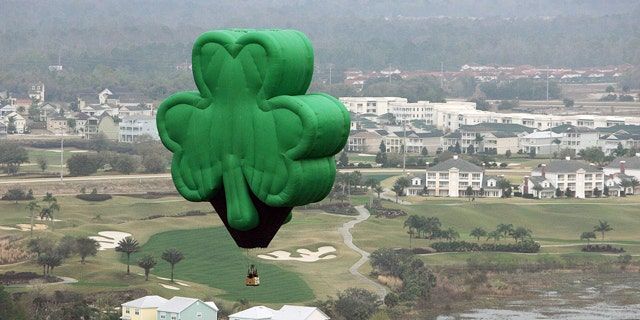 """A green shamrock hot-air balloon, named """"Paddy"""" and flown by Orlando Balloon Rides, drifts over Florida on St. Patrick's Day."""