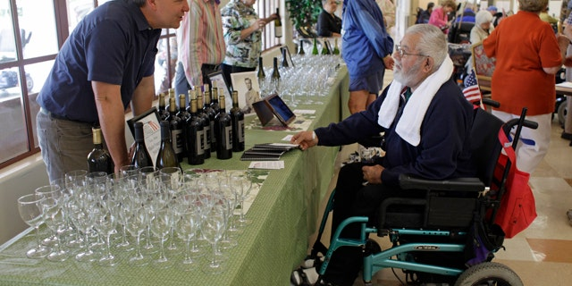 In this photo taken Sunday, April, 17, 2011, Andy Demsky, left, of Shafer Vineyards, talks with a veteran about the 2008 Merlot he was pouring during a lunch at the Veterans Home of California in Yountville, Calif.  The lunch included a program called Vintners for Veterans which provides high-quality wines to the men and women at the home to be enjoyed with their Sunday meal.  (AP Photo/Eric Risberg)