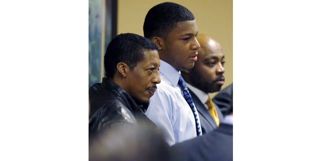 Ma'lik Richmond, center, stands with his father, Nathaniel Richmond, left, and attorney Walter Madison in Steubenville, Ohio, March 17, 2013.