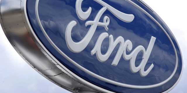 FILE - In this Thursday, June 5, 2014, file photo, clouds are reflected in the Ford sign at a dealership in Wexford, Pa. U.S. safety regulators have closed an investigation into steering problems in more than 500,000 Ford full-size cars without seeking a recall, the company announced Tuesday, Nov. 25, 2014. (AP Photo/Keith Srakocic, File)