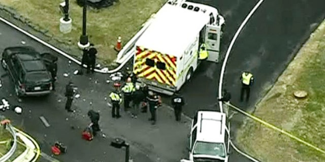 In this image made from video and released by WJLA-TV, authorities investigate the scene of a accident near a gate to Fort Meade, Md., on Monday, March 30, 2015. A spokesman at Fort Meade says two people are being treated for injuries at one of the gates of the sprawling Army installation near Baltimore. (AP Photo/WJLA-TV) MANDATORY CREDIT
