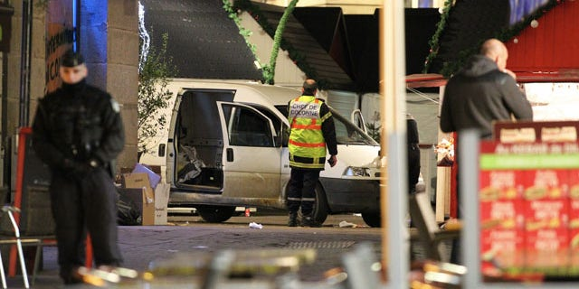 Dec. 22, 2014: A police officer guards the van that crashed into a French Christmas market in Nantes. French authorities urged calm after a series of attacks across the country left dozens of people injured, and said there was no evidence the attacks were connected by any terrorist motive. (AP Photo/Laetitia Notarianni)