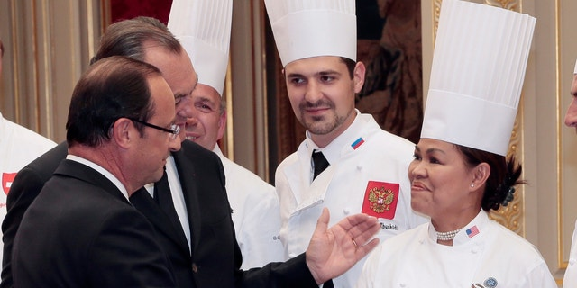 """July 24, 2012: French President Francois Hollande, left, shakes hands with Cristeta Comerford, chef at the White House, the US president official residence, as Vakhtang Abushidi, center, chef at the Kremlin in Moscow looks on during a reception at the Elysee palace in Paris, following the """"Chef des Chefs Club"""" (CCC) international meeting."""