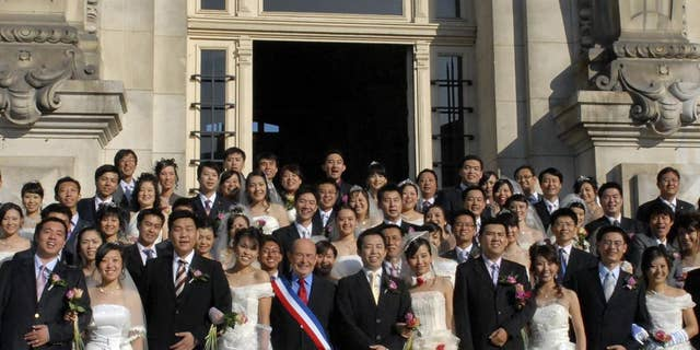 In this photo dated Oct. 2008, Tours mayor, Jean Germain, center, wearing a sash in the colors of the French flag, poses with a group of recently married Chinese couples in front of the city hall in Tours, France. Jean Germain  the former mayor of Tours has been found dead in a suspected suicide right as he was to go on trial over suspected kickbacks involving a spate of group weddings of Chinese visitors in the picturesque Loire Valley city. A defense lawyer said a half-dozen people are on trial over alleged kickbacks linked to euro750,000 ($815,000) that the city spent from 2008 to 2011 to lure Asian visitors _ some for weddings presided over by Germain while he was mayor. (AP Photo/Patrice Deschamps, la Nouvelle Republique) FRANCE OUT
