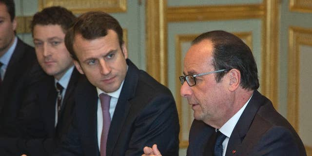 France's President Francois Hollande, right, and Economy Minister Emmanuel Macron, meet oil industry group leaders, on gasoline prices, at the Elysee Palace in Paris, Monday, Dec. 8, 2014. (AP Photo/Michel Euler, Pool)