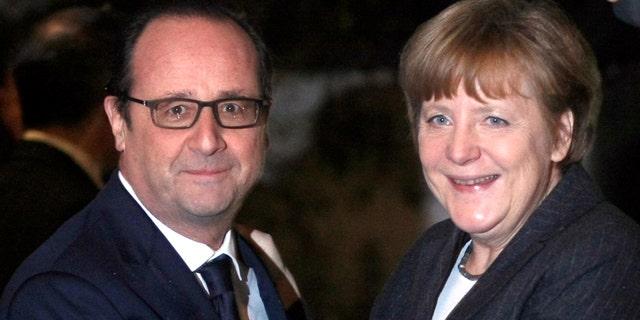 Jan. 30, 2015: French President Francois Hollande, left, greets German Chancellor Angela Merkel, prior to their informal dinner at the restaurant, Zum Ysehuet, in Strasbourg, France. (AP Photo/Christian Lutz, Pool)