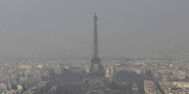 FILE - In this March 14, 2014 file photo, the Eiffel Tower, is photographed through the smog in Paris. Paris police have lowered speed limits and ordered a halt to trash burning Wednesday, March 18, 2015 as part of emergency measures triggered by a spike in air pollution — months before the city hosts a major international climate conference. (AP Photo/Jacques Brinon, File)