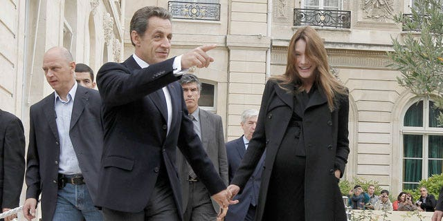 French President Nicolas Sarkozy, center, and his wife Carla Bruni-Sarkozy, left, walk in the gardens of the Elysee Palace in Paris during 28th edition of France's Day of Patrimony, Saturday, Sept. 17, 2011. France opens the doors of its state buildings as part of its Day of Patrimony when usually these buildings would be forbidden to the public.