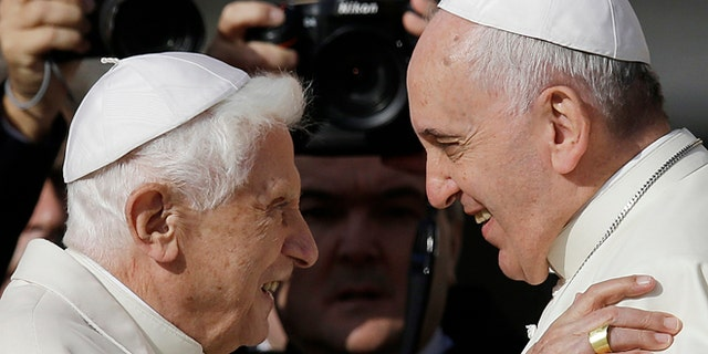 An ISIS propaganda video shows photos of Pope Benedict XVI, left, and Pope Francis being torn in half.