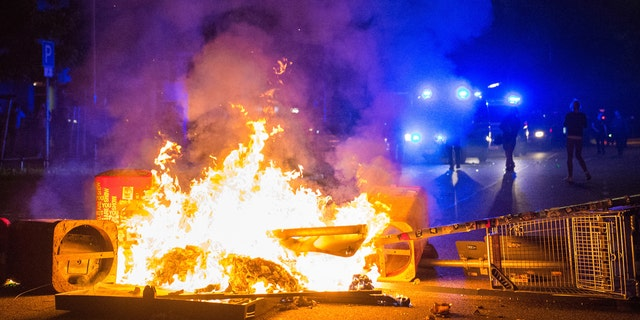 Policemen stand behind a burning barricade in the so-called 'Schanzenviertel' area, on the sidelines of the G-20 summit, early Sunday, July 9, 2017, in Hamburg. Rioters set up street barricades, looted supermarkets and attacked police with slingshots and firebombs. (Daniel Bockwoldt/dpa via AP)