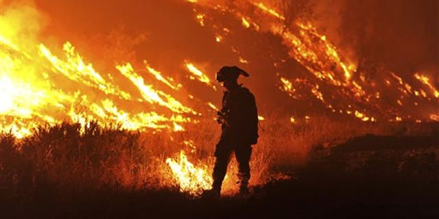 In this Aug. 3, 2015, file photo, CalFire Firefighter Bo Santiago lights a backfire as the Rocky fire burns near Clearlake, Calif. (AP Photo)