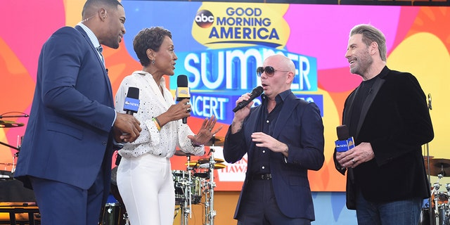 Travolta joins Pitbull on stage along with 'GMA' hosts Robin Roberts and Michael Strahan.