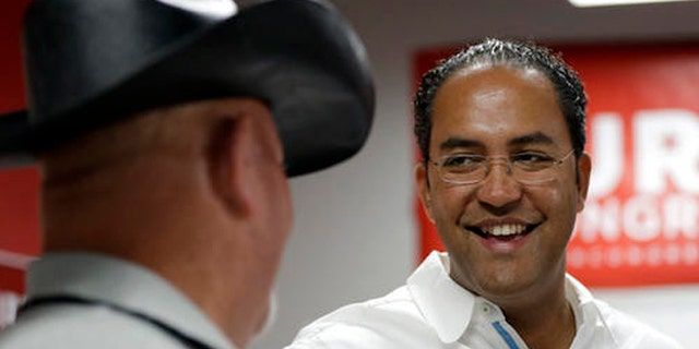 In this Saturday, Aug. 27, 2016, photo, first-term Republican Rep. Will Hurd, right, of Texas, talks with a supporter at a campaign office, in San Antonio.