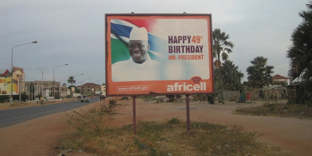 Dec. 31, 2014: A giant billboard of Gambia President Yahya Jammeh sits on an empty street during rush hour in Banjul. Two men have been charged in the United States with conspiring to help overthrow the Gambian government last week. (AP Photo)