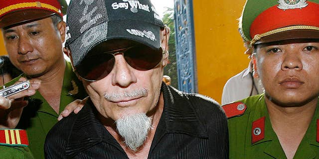 2006: Gary Glitter, former British rock singer, is led into court, Ho Chi Minh city, Vietnam. (AP)