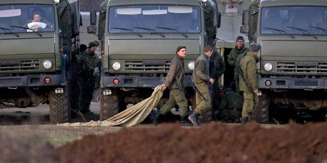 March 15, 2014: Pro-Russian soldiers walk past trucks that define the limits of their staging area in the vicinity of a Ukrainian military base in Perevalne, Ukraine.