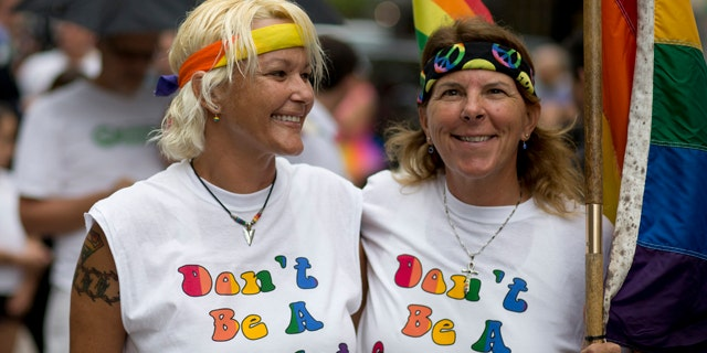 FILE - In this July 2, 2014, file photo, Kimmy Denny and her partner, Barb Lawrence of Palm Harbor, Fla., wait outside a court hearing on gay marriage in Miami. (AP Photo/J Pat Carter, File)