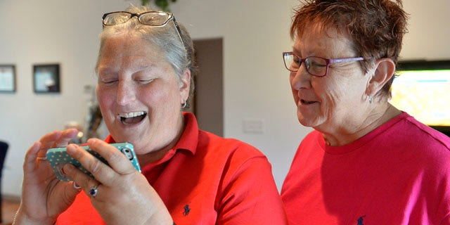 Aug. 26, 2015: April Miller, left, and her partner Karen Roberts read the decision of the United States Sixth Circuit Court of Appeals refusing to hear Rowan County Clerk Kim Davis' appeal that ordering her to issue marriage licenses is against her religious beliefs in Morehead, Ky. (AP Photo/Timothy D. Easley)