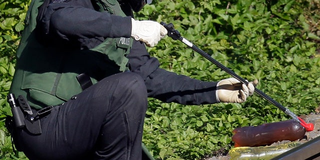 A police officer holds a bottle with unknown liqiod, part of a suspected explosive device at the rail tracks nearby the Suedkreuz station in Berlin, Germany, Thursday, Oct. 13, 2011. Sixteen firebombs have been found in nine locations since Monday and hundreds of trains have been delayed because of partial shutdowns, but there have been no injuries.