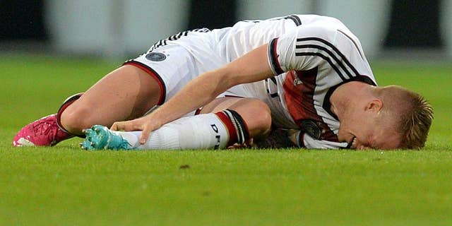 In this picture taken Friday June 6, 2014 German national soccer player  Marco Reus  lies on the pitch during the friendly soccer match between Germany and Armenia in Mainz Germany. Reus was helped off the pitch  after twisting his left ankle while challenging Artur Yedigaryan for the ball. Reus immediately dropped to the grass and appeared in considerable pain. Team doctor Hans-Wilhelm Mueller-Wohlfahrt shook his head as he assisted the Borussia Dortmund player off the pitch. Reus was taken to the hospital to determine the full extent of the injury. AP Photo/dpa,Thomas Eisenhuth)