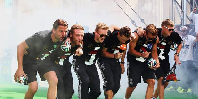 "German soccer players from left: Roman Weidenfeller, Shkodran Mustafi, Andre Schuerrle, Miroslav Klose, Mario Goetze and Toni Kroos celebrate on stage at the German team victory ceremony , near the Brandenburg Gate in Berlin,  Tuesday July 15,  2014.  Germany's World Cup winners shared their fourth title with hundreds of thousands of fans by parading the trophy through cheering throngs to celebrate at the Brandenburg Gate on Tuesday. An estimated 400,000 people packed the ""fan mile"" in front of the Berlin landmark to welcome home coach Joachim Loew's team and the trophy — which returned to Germany for the first time in 24 years. (AP Photo/ Alex Grimm,Pool)"