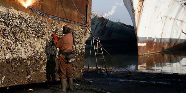 A worker uses a cutting torch to dismantle a barnacle-covered hull at the Galloo ship reycling plant in Belgium, Europe's largest
