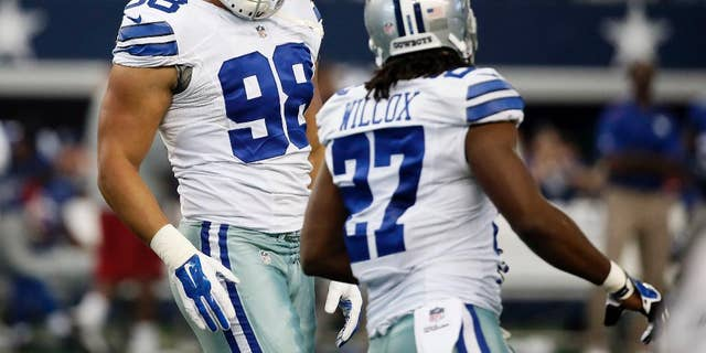 Dallas Cowboys defensive end Tyrone Crawford (98) and strong safety J.J. Wilcox (27) celebrate a defensive stop against the New York Giants during the first half of an NFL football game, Sunday, Oct. 19, 2014, in Arlington, Texas. (AP Photo/Brandon Wade)