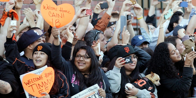 Oct. 29, 2012: San Francisco Giants fans cheer as the team buses arrive outside of AT&T Park in San Francisco.