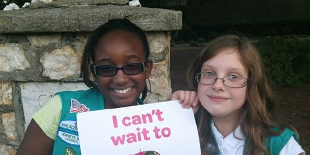 In this Sept. 27, 2013 photo provided by the Girl Scouts, Natalie Harrison, left, and Jasmine Barnett of Troop 2424 hold a promotional poster for their organization outside of Matthews Elementary School in Charlotte, N.C. The fifth graders were volunteering at a Girl Scout Informational night at the school to share their stories about their experiences in the group. Instead of placing ads on TV, in newspapers and on billboards, a decentralized campaign aimed at reversing a long-running decline in participation in the Girl Scouts will unfold in neighborhood initiatives and on social media as local councils directly target elementary school girls - even kindergartners - with promises of adventuresome fun. (AP Photo/Girl Scouts, Colleen Young)