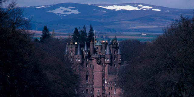 LOOKING DOWN THE MAIN DRIVEWAY TO GLAMIS CASTLE (THE CHILDHOOD HOME OF THE QUEEN MOTHER AND BIRTHPLACE OF PRINCESS MARGARET), WITH SNOW COVERED HILLS BEYOND, NORTH OF DUNDEE, ANGUS.