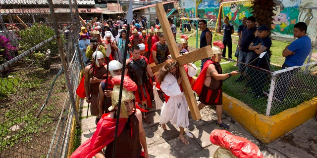 Inmate Aurelio Quevedo, carrying a cross, plays the role of Jesus during a reenactment of the Passion of Christ with fellow prisoners on Good Friday at the Mexico City Penitentiary during Holy Week in Mexico City, Friday, April 3, 2015. I behaved badly, Quevedo said in reference to his crime. But all of this leaves a good taste in the mouth, it generates repentance. Quevedo is a 37-year-old taxi driver serving a 49-year sentence for kidnapping. (AP Photo/Eduardo Verdugo)