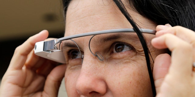 Dec. 3, 2013: Cecilia Abadie models her Google Glass as she talks with her attorney outside of traffic court in San Diego. When Abadie was pulled over on suspicion of speeding in October, the officer saw she was wearing Google Glass and tacked on a citation usually given to drivers who may be distracted by a video or TV screen. She pleaded not guilty to both charges on Tuesday.